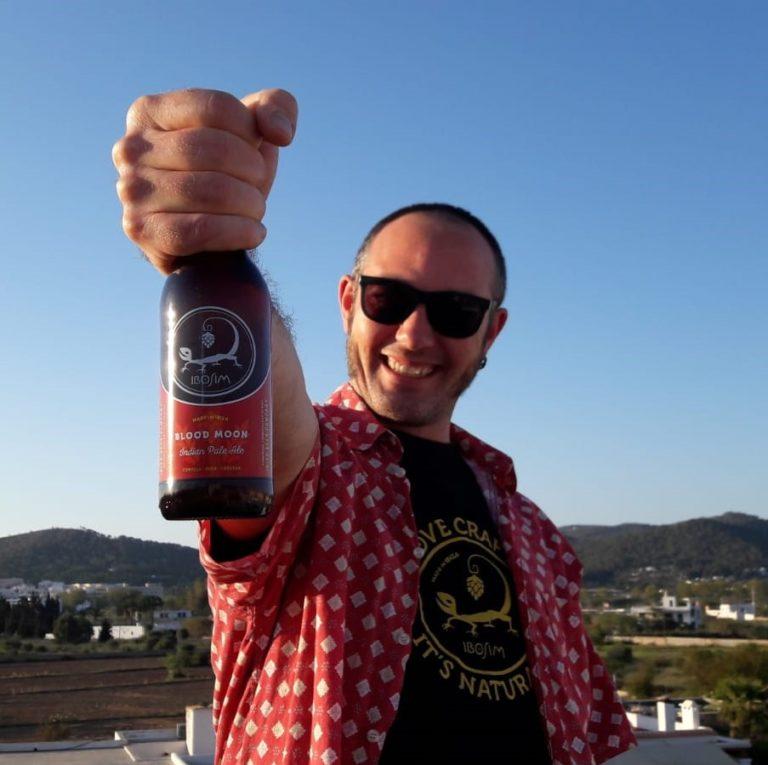 Victor levanta una botella de Ibosim Blood Moon IPA con vistas a la montaña